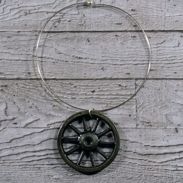 statement black necklace - vintage wheel neck cuff on grey concrete background