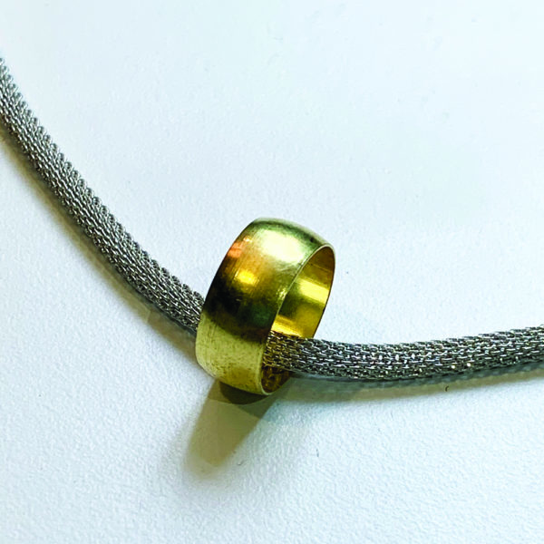 close up of steel and brass pendant